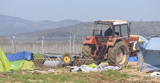 Traktorral tiporta el a migránsok sátrait a földjén egy gazda - videó