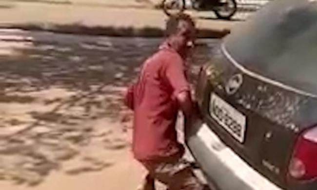 Bizarr felvétel: egy férfi a nyílt utcán szexelt egy autó kipufogójával