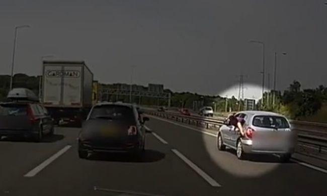 Kihajolt a kocsiból menet közben, hogy becsukja a tanksapkát - videó