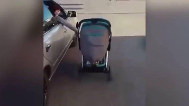 Az ablakon kihajolva tolta vezetés közben a babakocsit az anya - videó
